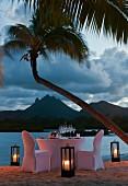 Festlich gedeckter Tisch mit weisser Husse am abendlichen Strand (Mauritius)