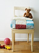 Patchwork quilt and teddy bear on a wooden chair