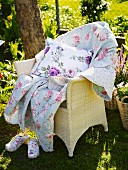 Wicker chair with a quilt and pillows in the garden
