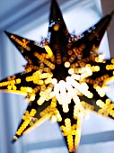 Star-shaped lantern (Christmas decoration) in front of a window