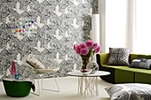 Mix of furniture styles in front of black and white patterned wallpaper