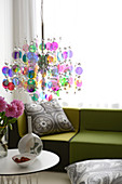 Pendant lamp made of colourful discs above side table in front of green sofa