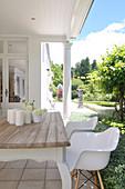 weiße Schalenstühle am rustikalen Holztisch auf Veranda vor Haus im Kolonialstil