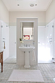 Renovated bathroom with pedestal washstand against partition and spacious shower area