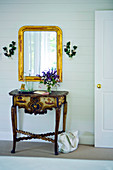 Antique, carved console table below gilt-framed mirror in rustic foyer