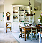 Chandelier hanging above set table in front of dresser against partition in rustic dining room