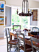 Chandelier hanging above set table in front of open door with view of garden
