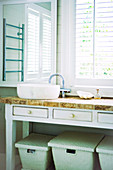 Washing baskets stored beneath rustic washstand with drawers in bathroom