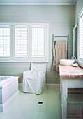 Chair with cover below window with closed shutters in rustic bathroom