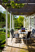 Table and chairs beneath pergola with climbers adjoining country house