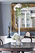 White flowers in different vases and decorative spheres on antique table in front of gilt-framed mirror on wall