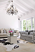 Couch with black and white striped cover and animal-skin rug on floor of simple, renovated country house