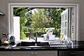 Kitchen counter beneath open window with view of garden