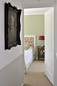 Anteroom with picture on wall and open door looking into bedroom