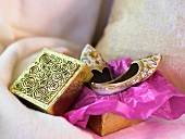 Moroccan gloves on violet paper and a decorated wooden box on a cushion
