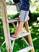Lady standing on a wooden ladder
