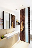 Brown and beige bathroom with two sinks and partition screening bathtub