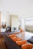 Elegantes Wohnzimmer mit Ecksofa, Kamin und Panoramablick auf die Landschaft