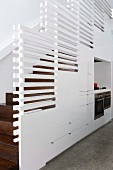 Installation below stairs and balustrade of white, horizontal wooden slats