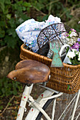An old leather saddle on a vintage white bicycle, with a basket of garden utensils on the pannier rack