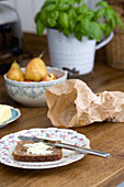 A slice of bread and butter on a nostalgic floral-patterned plate, next to a crumpled paper bag