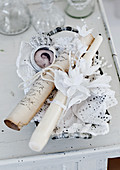 Rolled writing paper, silk flowers and lace in dish