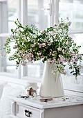 Bouquet of garden flowers in white china jug on half-height cabinet