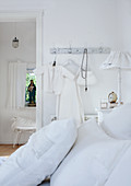 White pillows on bed and child's clothing hanging on wall hooks