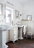 Rustic, vintage-style bathroom with twin pedestal sinks and half-height cabinet below window