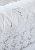 White fabric with lace edging and embroidered monogram