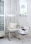 Corner of room in white-painted, wooden cabin with cushions on old rocking chair next to rusty metal chair