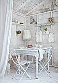 Corner of room in white-painted wooden cabin with white kitchen table and simple garden chairs