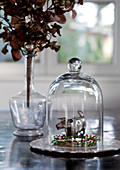 Small brass cow on flower meadow under bell jar
