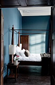 Antique canopied bed next to bedside table in blue-painted bedroom of old hunting lodge