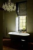 Dim period building bathroom with nostalgic chandelier and free-standing vintage bathtub below window