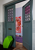 Mixture of colours and styles - grass green sculpture leaning on dove grey period door with view of pink painting and lilac rug in large, modern hallway