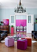 Gelungene Mischung aus Design Klassikern und Antiquitäten im Altbauwohnzimmer, dazu weisse Panton-Chairs vor pinkfarbenem Kunstwerk im Esszimmer