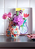 Still-life in kitchen - tulips in ceramic vase with floral decoration and child's drawing of vase of flowers