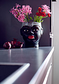 Vase in the shape of a black woman's head filled with summer flowers and red onions on kitchen worksurface