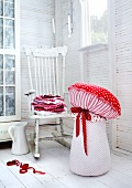 Decorative toadstools in a the corner of a white room with a vintage swivel chair and porcelain pitcher