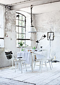 Dining table with tablecloth and white chairs in front of lattice window in dilapidated room in former factory