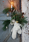 Advent arrangement of mittens, branches, baubles and pine cones on door