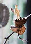 Miniature figurine in nut shell on twig