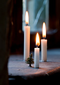 Three white candles on simple window sill