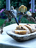 Candlestick with stylised leaf garlands and china budgerigar ornaments above stone platter of olive bread