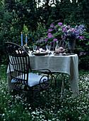 Romantisch gedeckter Tisch mit Kerzenlicht und Blumenstrauss im Garten