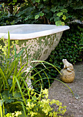 Stone frog next to old bathtub in garden
