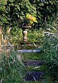Säule mit einem Korb Blumen im Garten