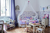 Rustic children's chairs and table in front of canopied bed in spacious child's bedroom with half-height patterned wallpaper