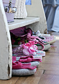 Children's shoes on parquet flooring in front of white shelves
